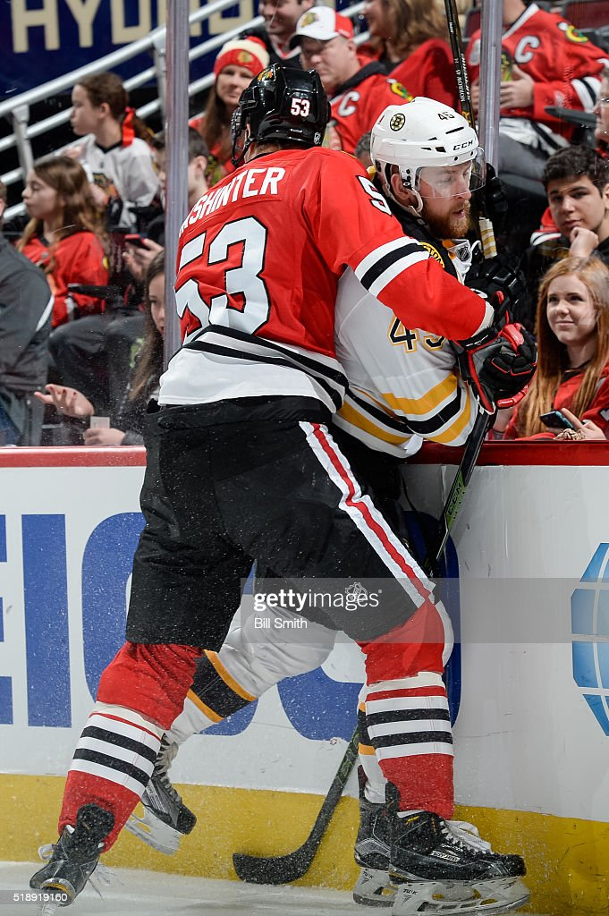 Brandon Mashinter of the Chicago Blackhawks hits Joe Morrow of the Boston Bruins in the third period of the NHL game at the United Center on April 3...