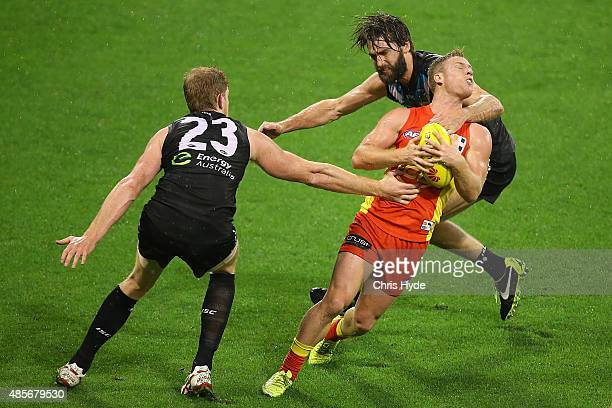 Brandon Matera of the Suns is tackled by Justin Westhoff of the Power during the round 22 AFL match between the Gold Coast Suns and the Port Adelaide...