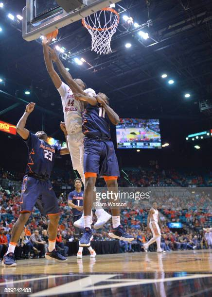 Brandon McCoy of the UNLV Rebels battles for a rebound against Aaron Jordan and Greg Eboigbodin of the Illinois Fighting Illini during their game at...