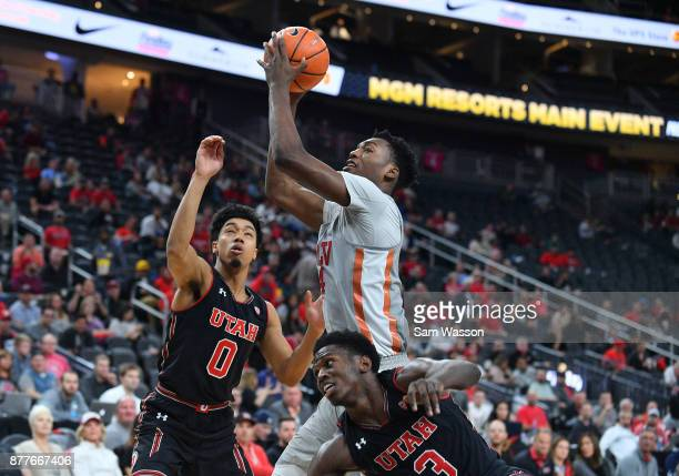 Brandon McCoy of the UNLV Rebels drives to the basket against Sedrick Barefield and Donnie Tillman of the Utah Utes during the championship game of...