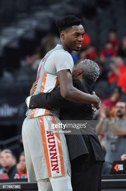 Brandon McCoy of the UNLV Rebels hugs head coach Marvin Menzies of the UNLV Rebels after coming out of the game against the Utah Utes during the...