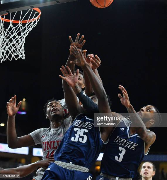 Brandon McCoy of the UNLV Rebels Tim Harrison and Ako Adams of the Rice Owls battle for a rebound during day one of the Main Event basketball...