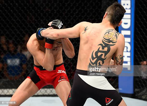 Brandon Moreno of Mexico punches Louis Smolka in their flyweight bout during the UFC Fight Night event at the Moda Center on October 1 2016 in...