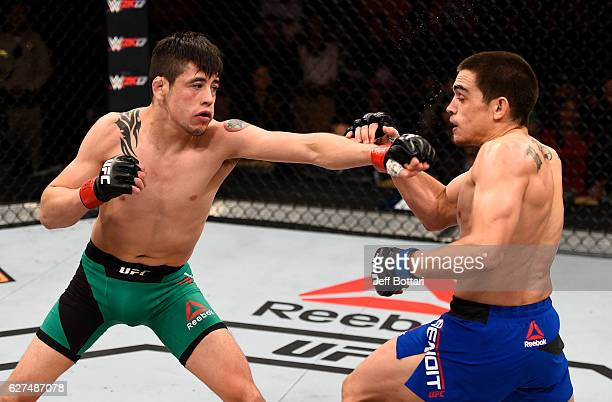 Brandon Moreno of Mexico punches Ryan Benoit in their flyweight bout during The Ultimate Fighter Finale event inside the Pearl concert theater at the...