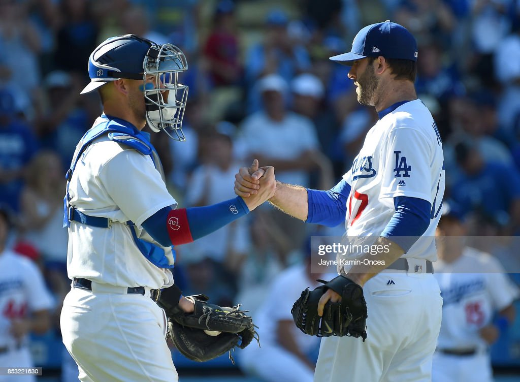 Brandon Morrow #17 shakes hands with Yasmani Grandal #9 of the Los Angeles Dodgers after earning a save in the ninth inning of the game against the San Francisco Giants at Dodger Stadium on September 24, 2017 in Los Angeles, California.