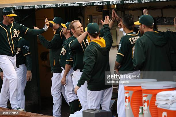 Brandon Moss and Craig Gentry of the Oakland Athletics are greeted in the dugout during the game against the Seattle Mariners at Oco Coliseum on May...