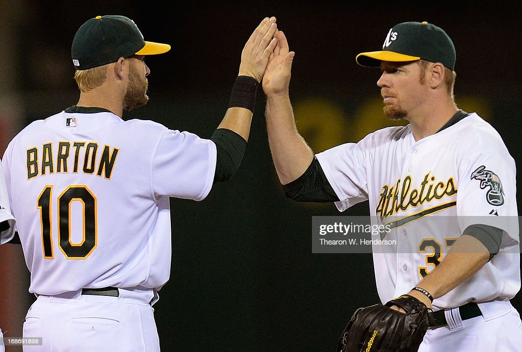 <a gi-track='captionPersonalityLinkClicked' href=/galleries/search?phrase=Brandon+Moss&family=editorial&specificpeople=702783 ng-click='$event.stopPropagation()'>Brandon Moss</a> #37 and <a gi-track='captionPersonalityLinkClicked' href=/galleries/search?phrase=Daric+Barton&family=editorial&specificpeople=682626 ng-click='$event.stopPropagation()'>Daric Barton</a> #10 of the Oakland Athletics celebrates defeating the Texas Rangers 5-1 at O.co Coliseum on May 13, 2013 in Oakland, California.