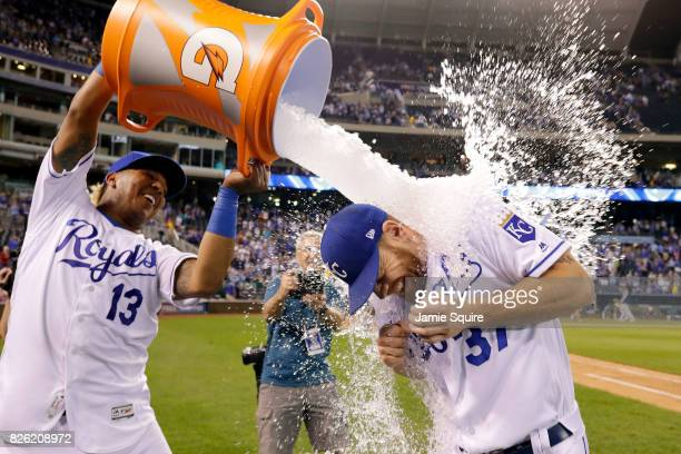 Brandon Moss of the Kansas City Royals is doused with water by catcher Salvador Perez as Kansas City Star photographer John Sleezer looks on after...