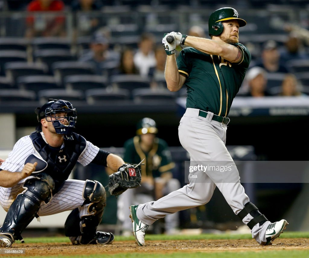 Brandon Moss #37 of the Oakland Athletics hits a solo home run in the 10th inning as Brian McCann #34 of the New York Yankees defends on June 3, 2014 at Yankee Stadium in the Bronx borough of New York City.