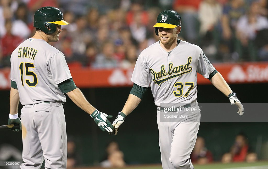 Brandon Moss #37 of the Oakland Athletics is greeted by Seth Smith #15 as Moss returns to the dugout after hitting a solo home run in the fifth inning against the Los Angeles Angels of Anaheim at Angel Stadium of Anaheim on April 10, 2013 in Anaheim, California.