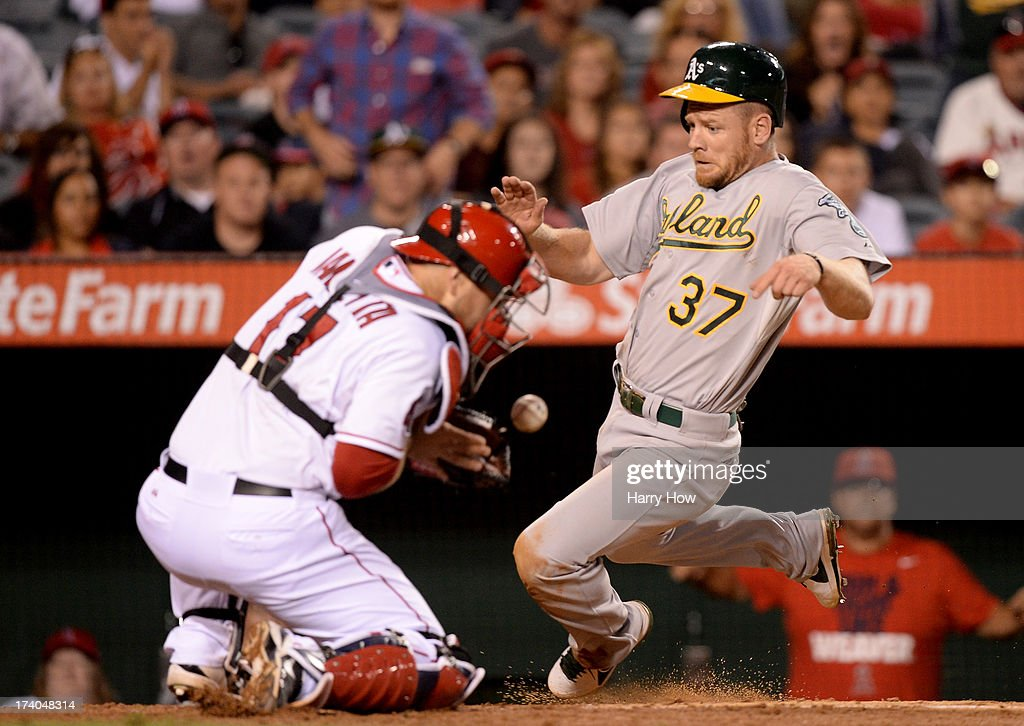 <a gi-track='captionPersonalityLinkClicked' href=/galleries/search?phrase=Brandon+Moss&family=editorial&specificpeople=702783 ng-click='$event.stopPropagation()'>Brandon Moss</a> #37 of the Oakland Athletics scores a run in front of <a gi-track='captionPersonalityLinkClicked' href=/galleries/search?phrase=Chris+Iannetta&family=editorial&specificpeople=836137 ng-click='$event.stopPropagation()'>Chris Iannetta</a> #17 of the Los Angeles Angels to trail 4-1 during the ninth inning at Angel Stadium of Anaheim on July 19, 2013 in Anaheim, California.