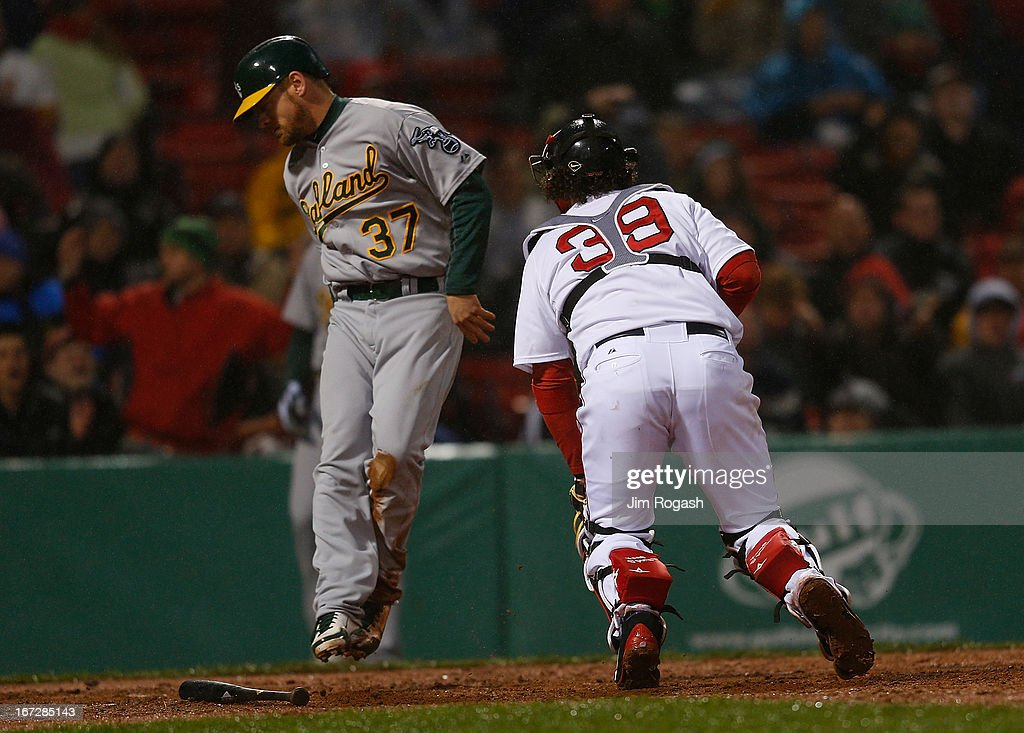 Brandon Moss #37 of the Oakland Athletics scores as Jarrod Saltalamacchia #39 of the Boston Red Sox prepares to chase an errant throw to the plate by Alfredo Aceves #91 of the Boston Red Sox in the 3rd inning at Fenway Park on April 23, 2013 in Boston, Massachusetts.