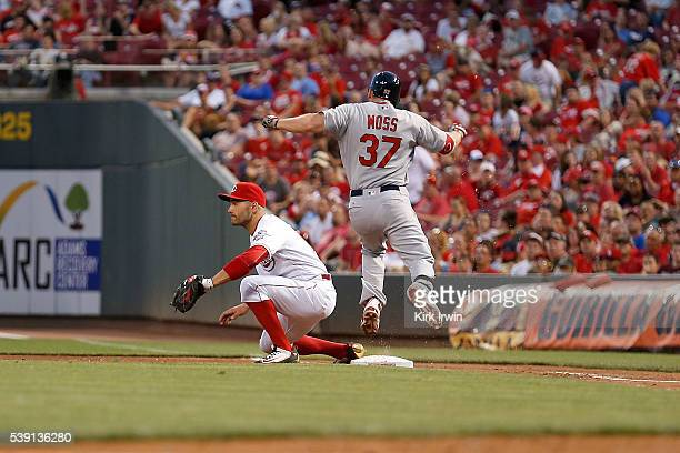 Brandon Moss of the St Louis Cardinals reaches first base before the throw can get to Joey Votto of the Cincinnati Reds during the seventh inning at...