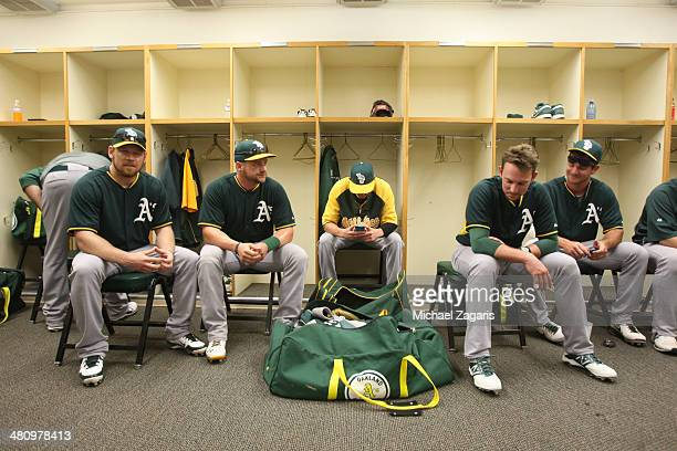 Brandon Moss Stephen Vogt Jed Lowrie and John Jaso of the Oakland Athletics relax in the dugout prior to a spring training game against the Los...