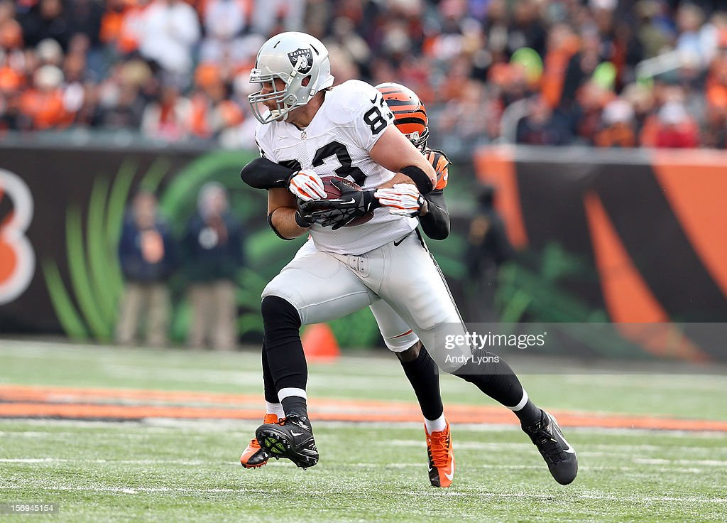 Brandon Myers #83 of the Oakland Raiders is tackled by <a gi-track='captionPersonalityLinkClicked' href=/galleries/search?phrase=Reggie+Nelson&family=editorial&specificpeople=2141088 ng-click='$event.stopPropagation()'>Reggie Nelson</a> #20 of the Cincinnati Bengals during the NFL game at Paul Brown Stadium on November 25, 2012 in Cincinnati, Ohio.
