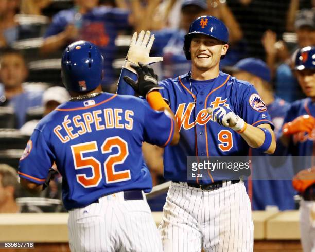 Brandon Nimmo of the New York Mets congratulates Yoenis Cespedes after they both scored in the sixth inning against the Miami Marlins on a hit by...