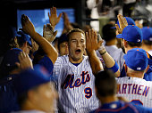 Brandon Nimmo of the New York Mets is congratulated by teammates in the dugout after he hit his first major league home run in the fourth inning...