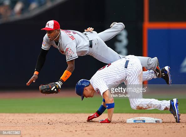Brandon Nimmo of the New York Mets is safe at second base as he rolls into shortstop Adeiny Hechavarria of the Miami Marlins allowing Travis d'Arnaud...