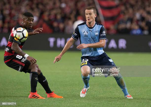 Brandon O'Neill of Sydney FC chips the ball past Wanderers Rolieny Bonevacia during the round three ALeague match between Sydney FC and Western...