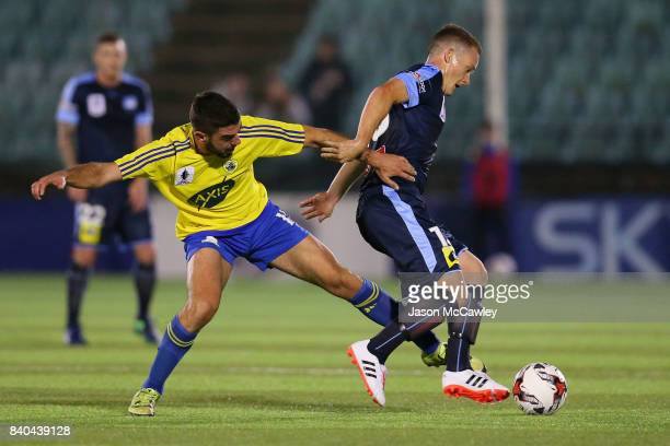 Brandon O'Neill of Sydney is challenged by Perry Moustakas of the Berries during the round of 16 FFA Cup match between the Bankstown Berries and...