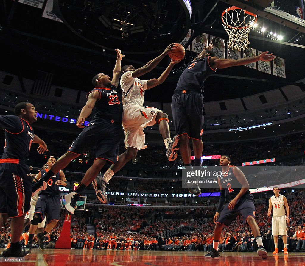 Brandon Paul #3 of the Illinois Fighting Illini goes up between Frankie Sullivan #23 and Shaquille Johnson #5 of the Auburn Tigers at United Center on December 29, 2012 in Chicago, Illinois. Illinois defeated Auburn 81-79.