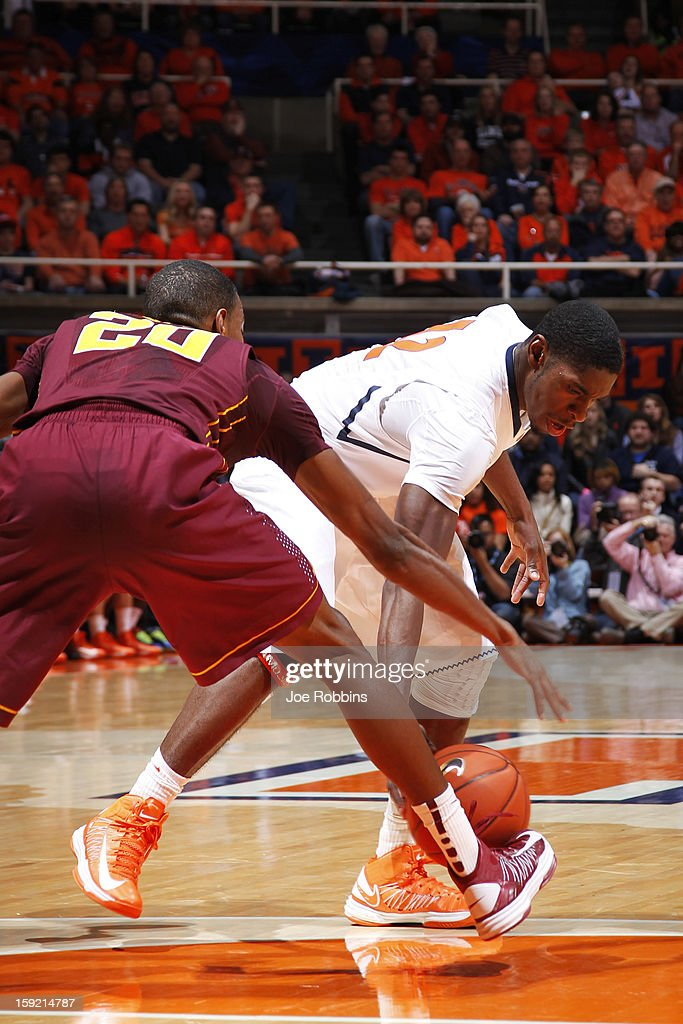 Brandon Paul #12 of the Illinois Fighting Illini has the ball knocked loose by Austin Hollins #20 of the Minnesota Golden Gophers during the game at Assembly Hall on January 9, 2013 in Champaign, Illinois.