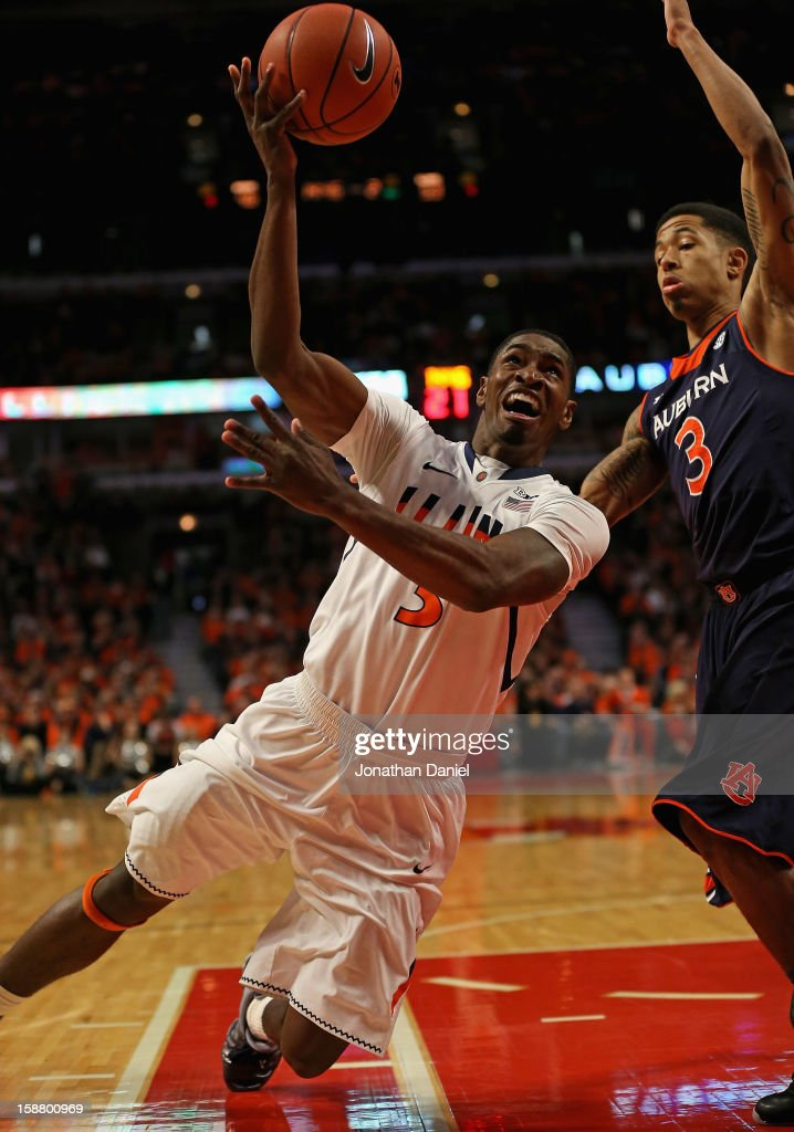 Brandon Paul #3 of the Illinois Fighting Illini hits a shot while falling down against Chris Denson #3 of the Auburn Tigers at United Center on December 29, 2012 in Chicago, Illinois. Illinois defeated Auburn 81-79.