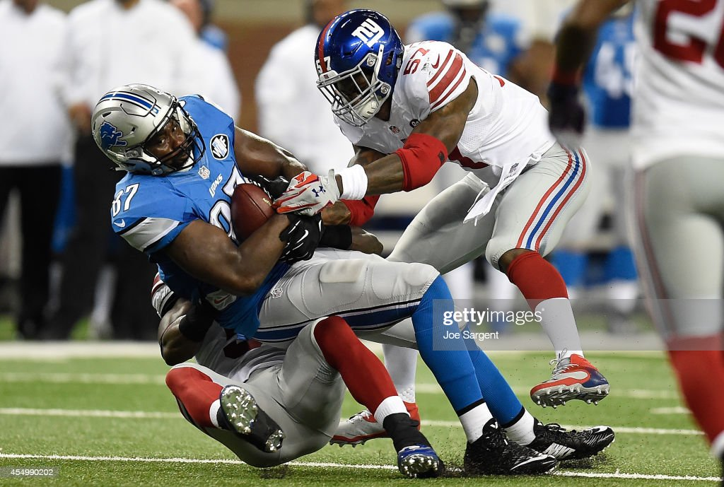 Brandon Pettigrew of the Detroit Lions is brought down in the first quarter by Jon Beason and Jacquian Williams of the New York Giants during a game...