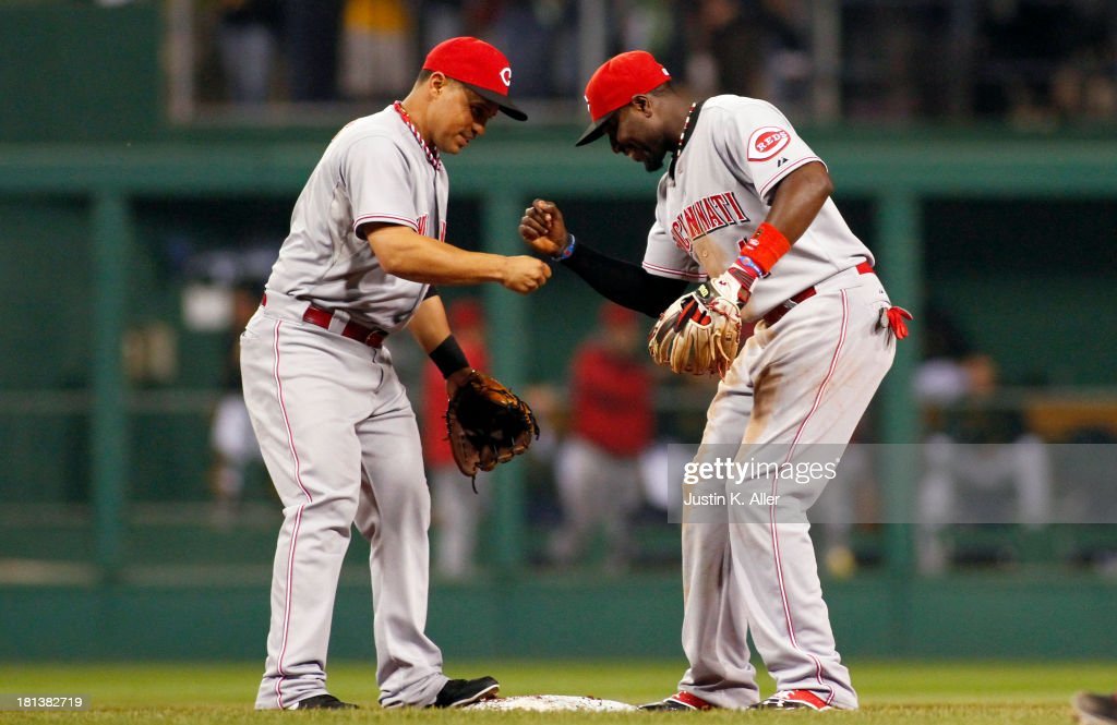Brandon Phillips #4 and <a gi-track='captionPersonalityLinkClicked' href=/galleries/search?phrase=Cesar+Izturis&family=editorial&specificpeople=203148 ng-click='$event.stopPropagation()'>Cesar Izturis</a> #3 of the Cincinnati Reds celebrate after defeating the Pittsburgh Pirates 6-5 in 10 innings on September 20, 2013 at PNC Park in Pittsburgh, Pennsylvania.