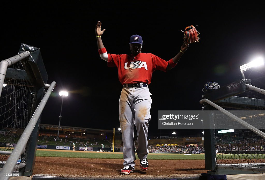 Brandon Phillips #4 of Team USA holds up his arms as he walks into the dugout during the spring training game against the Colorado Rockies at Salt River Fields at Talking Stick on March 6, 2013 in Scottsdale, Arizona.