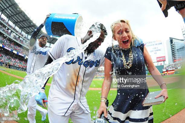 Brandon Phillips of the Atlanta Braves is doused by Matt Kemp with a water cooler along with Braves reporter Kelsey Wingert after kocking in the...