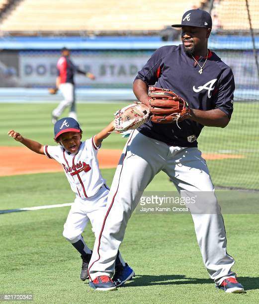 Brandon Phillips of the Atlanta Braves plays with his four year old son Micah Phillipsduring batting practice before the game against the Los Angeles...