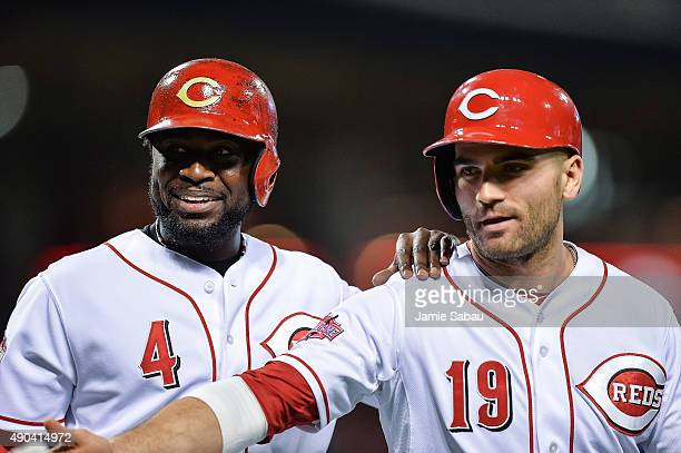 Brandon Phillips of the Cincinnati Reds and Joey Votto of the Cincinnati Reds celebrate after scoring against the New York Mets at Great American...
