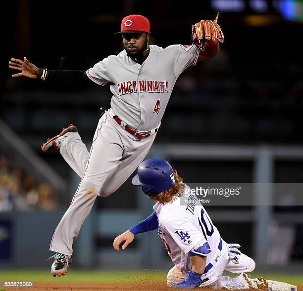 Brandon Phillips of the Cincinnati Reds avoids a slide from Justin Turner of the Los Angeles Dodgers as he turns a double play during the eighth...