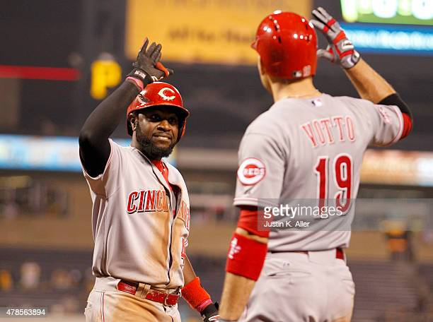 Brandon Phillips of the Cincinnati Reds celebrates with Joey Votto after hitting a solo home run in the thirteenth inning during the game against the...