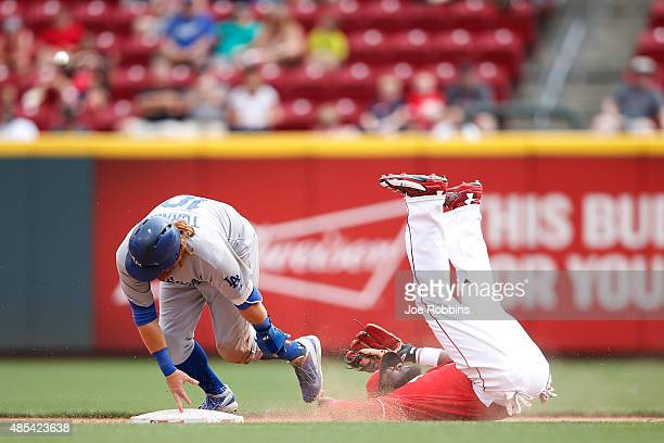 Brandon Phillips of the Cincinnati Reds falls backward while trying to field the ball as Justin Turner of the Los Angeles Dodgers slides safely into...