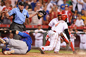 Brandon Phillips of the Cincinnati Reds is called safe by umpire Mike Winters for the tying run in the bottom of the ninth inning after beating the...