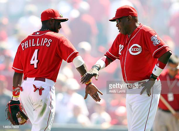 Brandon Phillips of the Cincinnati Reds is congratulated by manager Dusty Baker following the interleague game against the Cleveland Indians at Great...