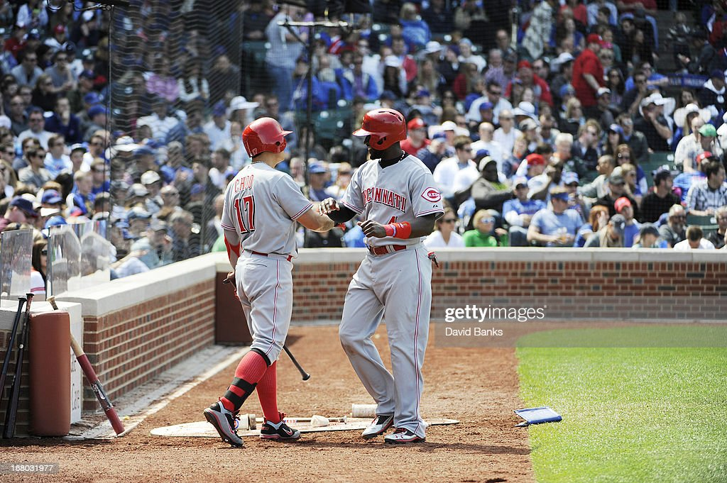 Brandon Phillips #4 of the Cincinnati Reds is greeted by Shin-Soo Choo #17 after scoring against the Chicago Cubs during the eighth inning on May 4, 2013 at Wrigley Field in Chicago, Illinois.