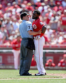 Brandon Phillips of the Cincinnati Reds is restrained by homeplate umpire DJ Reyburn after being hit by a pitch in the 8th inning against the...