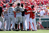 Brandon Phillips of the Cincinnati Reds is restrained by Manager Bryan Price after being hit by a pitch in the 8th inning against the Pittsburgh...