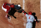 Brandon Phillips of the Cincinnati Reds is tagged out at home plate by catcher Henry Blanco of the Arizona Diamondbacks as he attempts to score...