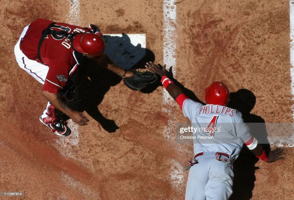 Brandon Phillips #4 of the Cincinnati Reds is tagged out at home plate by catcher <a gi-track='captionPersonalityLinkClicked' href=/galleries/search?phrase=Henry+Blanco&family=editorial&specificpeople=211366 ng-click='$event.stopPropagation()'>Henry Blanco</a> #12 of the Arizona Diamondbacks as he attempts to score during the second inning of the Major League Baseball game at Chase Field on April 10, 2011 in Phoenix, Arizona. The Diamondbacks defeated the Reds 10-8.