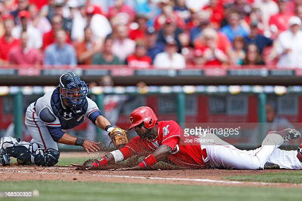 Brandon Phillips of the Cincinnati Reds is tagged out at home plate trying to score in the second inning by Gerald Laird of the Atlanta Braves during...