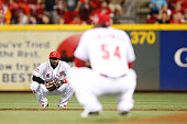 Brandon Phillips of the Cincinnati Reds looks at Aroldis Chapman as he reacts after throwing a wild pitch and allowing a run to score in the ninth...