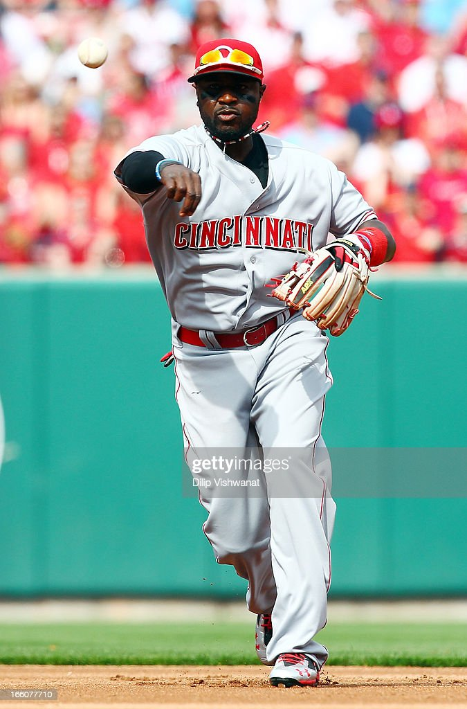 : Brandon Phillips #4 of the Cincinnati Reds sends the ball to first against the St. Louis Cardinals during Opening Day on April 8, 2013 at Busch Stadium in St. Louis, Missouri.