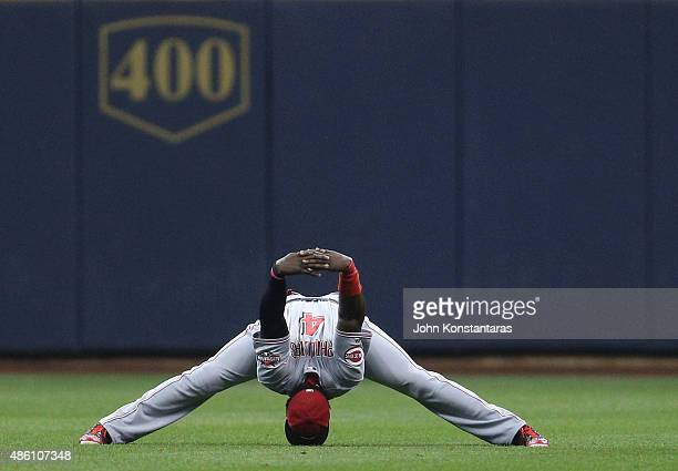 Brandon Phillips of the Cincinnati Reds stretches in the outfield before their game against the Milwaukee Brewers at Miller Park on August 29 2015 in...