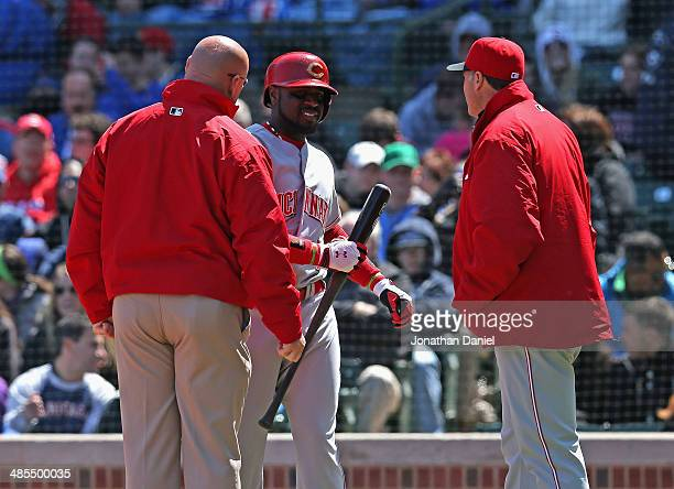 Brandon Phillips of the Cincinnati Reds talks with a trainer and manager Bryan Price after apparently hurting his back batting against the Chicago...
