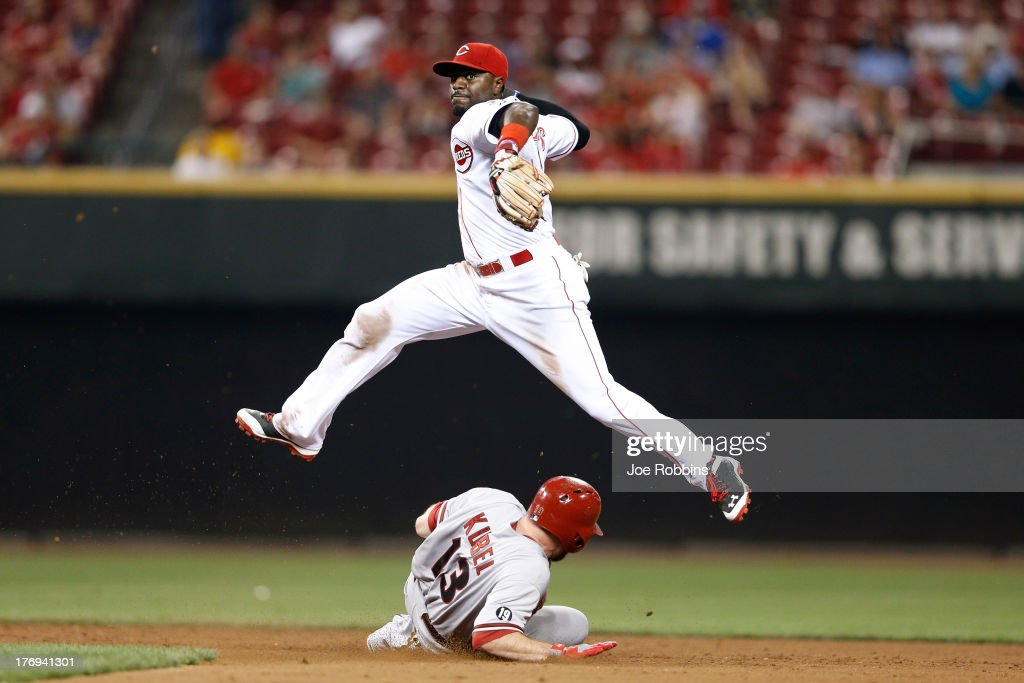 Brandon Phillips #4 of the Cincinnati Reds turns a double play in the ninth inning against <a gi-track='captionPersonalityLinkClicked' href=/galleries/search?phrase=Jason+Kubel&family=editorial&specificpeople=575883 ng-click='$event.stopPropagation()'>Jason Kubel</a> #13 of the Arizona Diamondbacks during the game at Great American Ball Park on August 19, 2013 in Cincinnati, Ohio. The Reds won 5-3.
