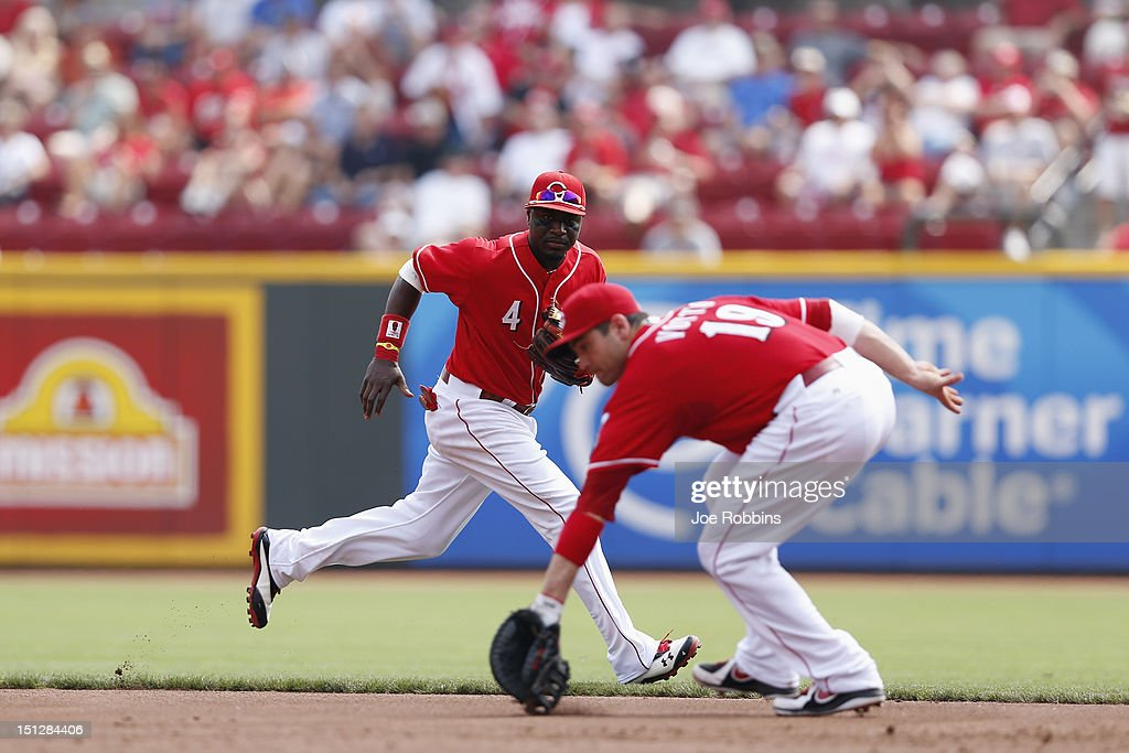 Brandon Phillips #4 of the Cincinnati Reds watches as <a gi-track='captionPersonalityLinkClicked' href=/galleries/search?phrase=Joey+Votto&family=editorial&specificpeople=759319 ng-click='$event.stopPropagation()'>Joey Votto</a> #19 fields a ground ball during the game against the Philadelphia Phillies at Great American Ball Park on September 5, 2012 in Cincinnati, Ohio. The Phillies won 6-2.